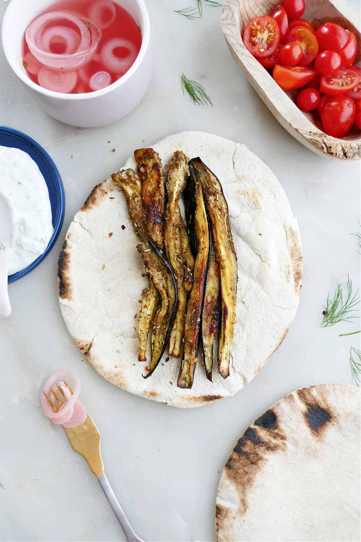 roasted eggplant strips placed in the center of pita bread next to other ingredients
