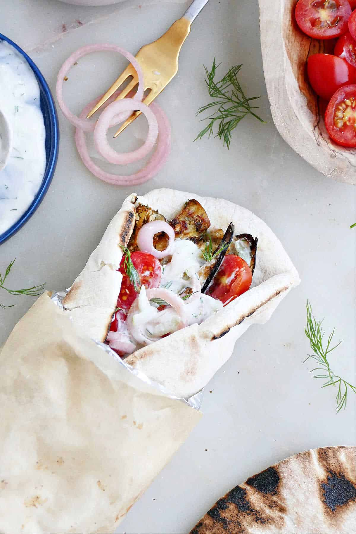 eggplant gyro sandwich on pita wrapped up in foil and parchment paper next to toppings