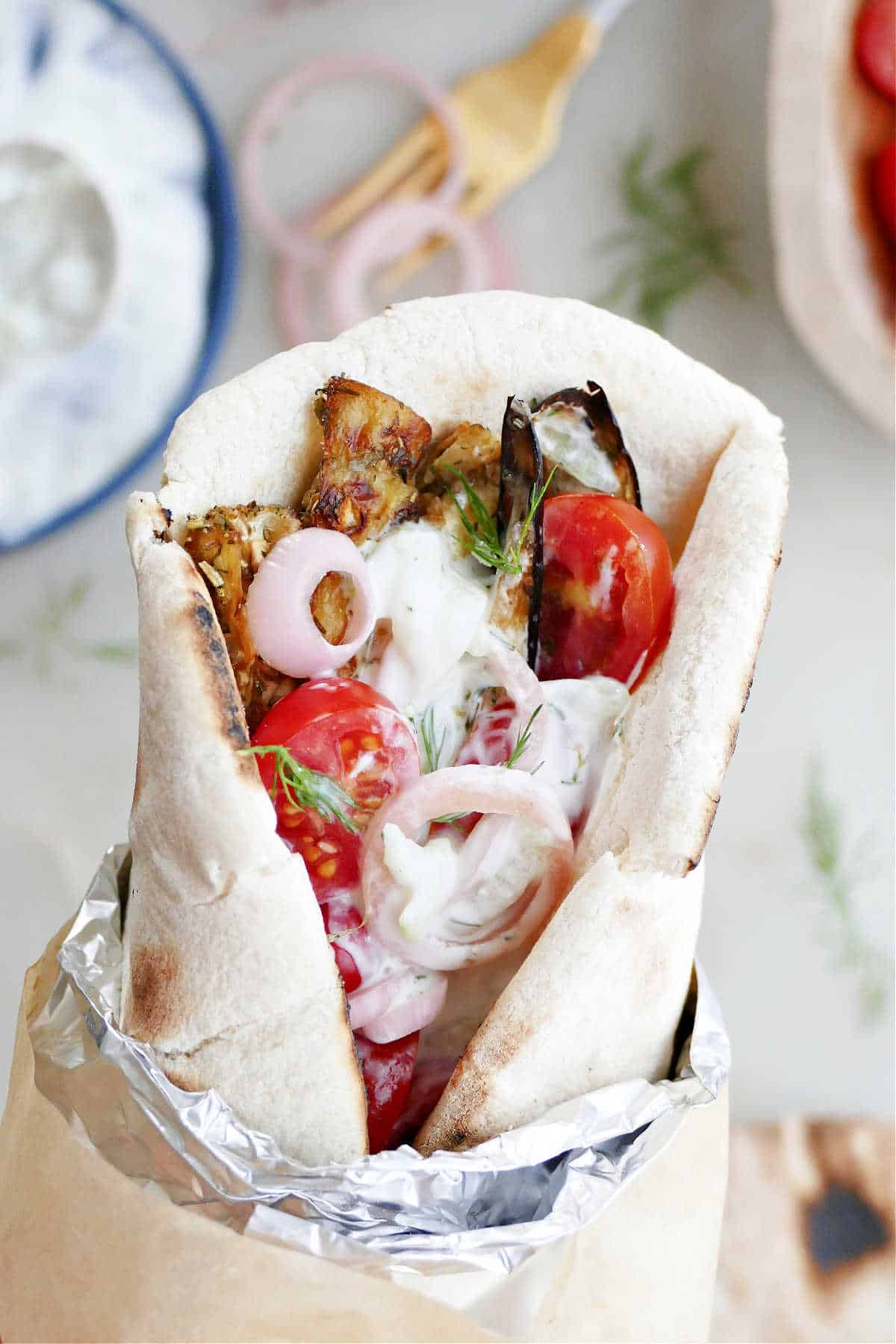 woman holding an eggplant gyro sandwich wrapped in foil and paper over a counter