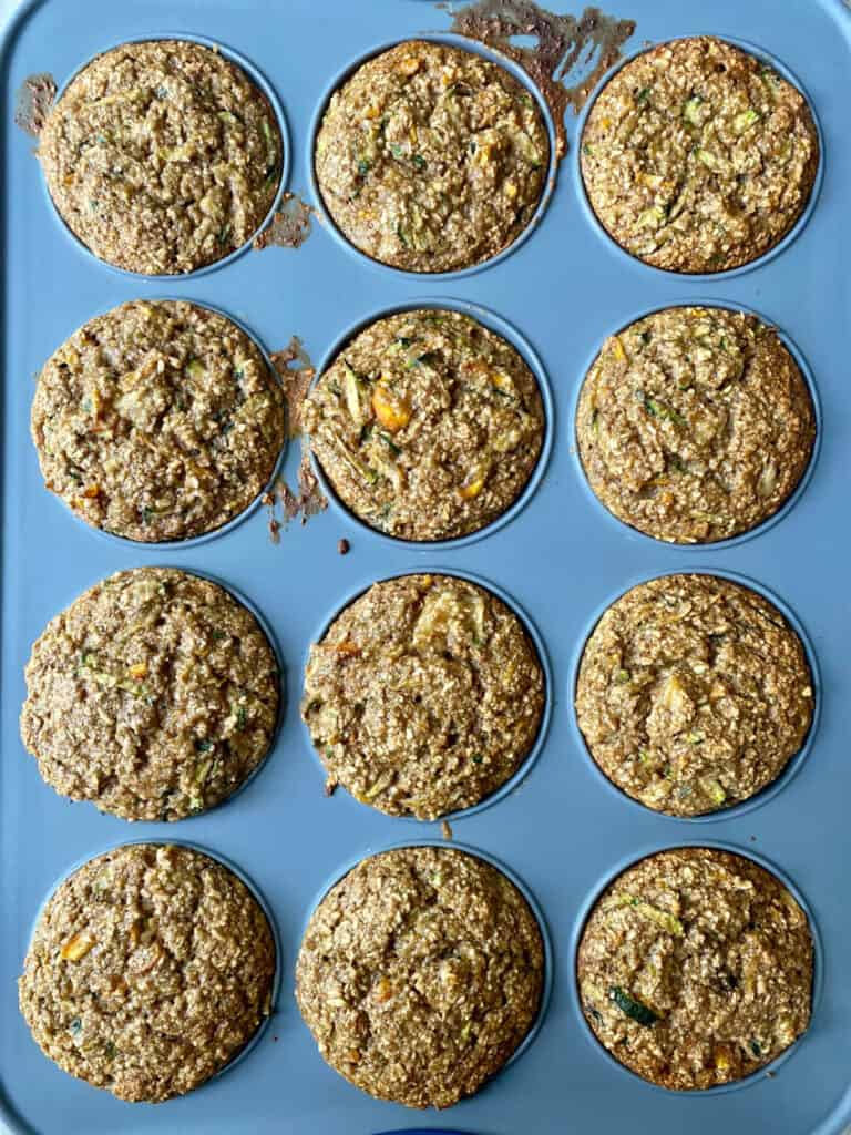 muffin tin with zucchini carrot oat muffins after being pulled out of the oven