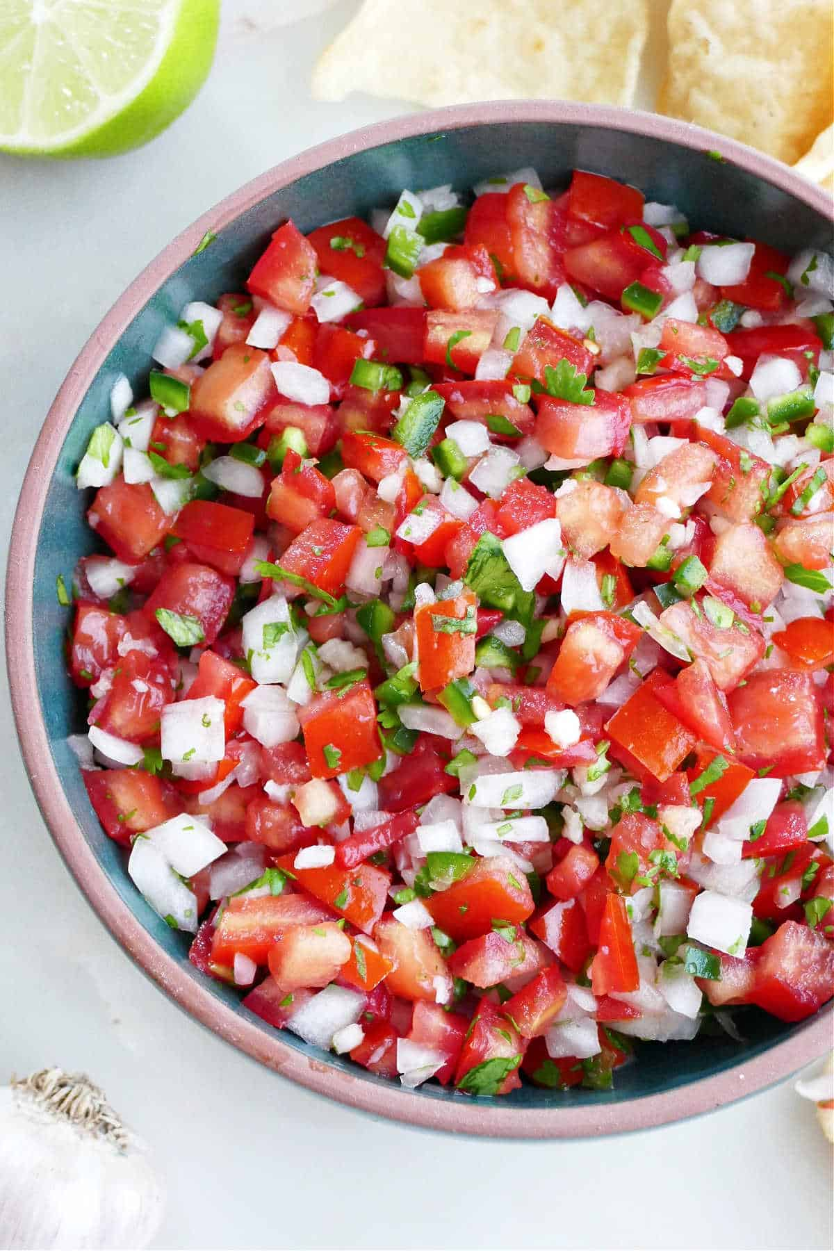 garden salsa with jalapeno, onion, and cilantro in a serving bowl next to chips