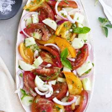 heirloom tomato and cucumber salad topped with fresh herbs on a serving platter