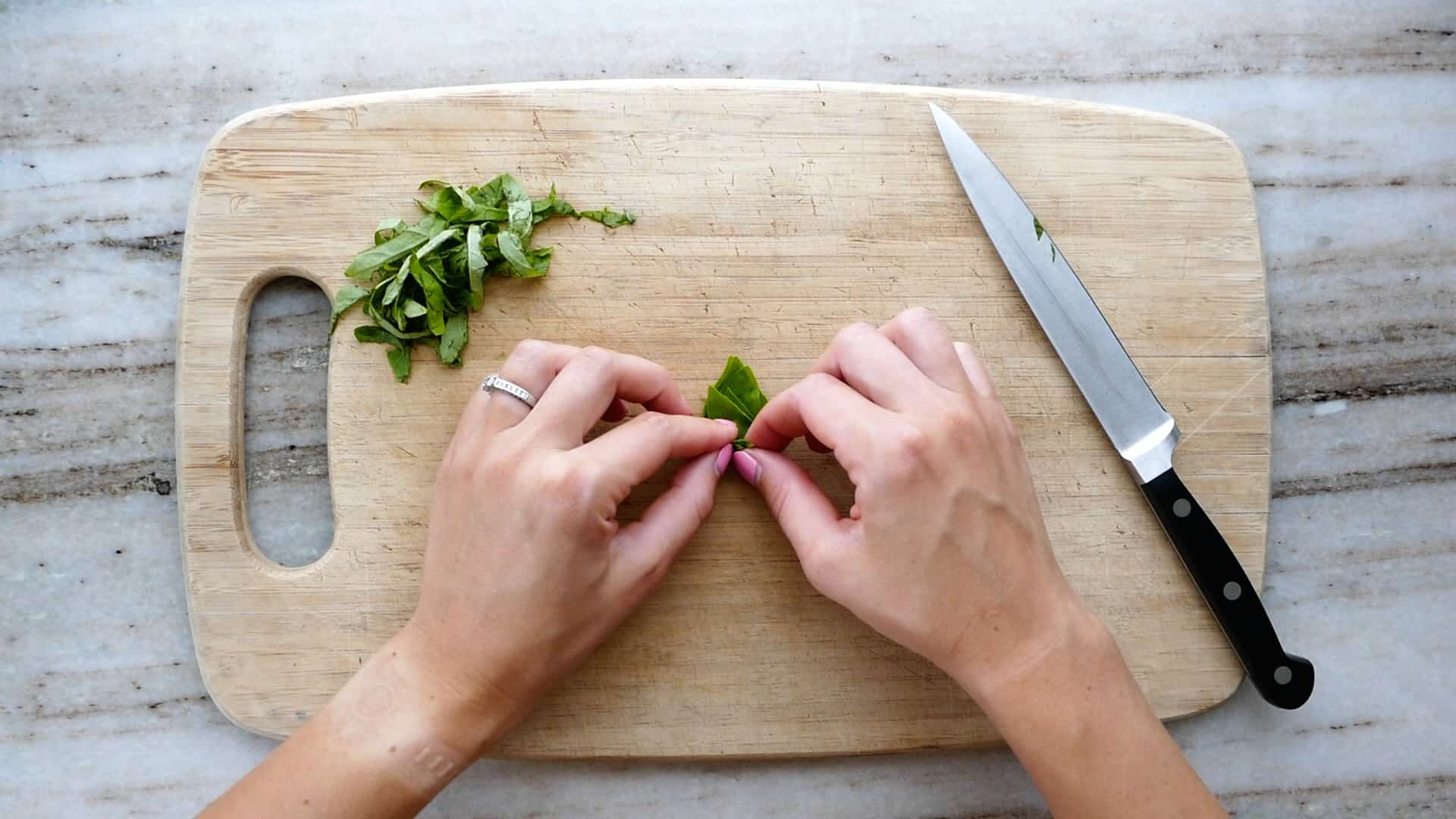 woman rolling up basil leaves on a cutting board