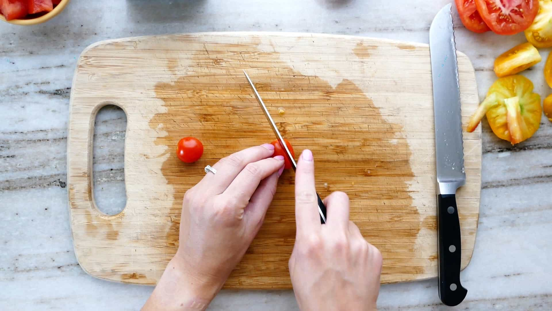 woman cutting cherry tomatoes in half on a cutting board