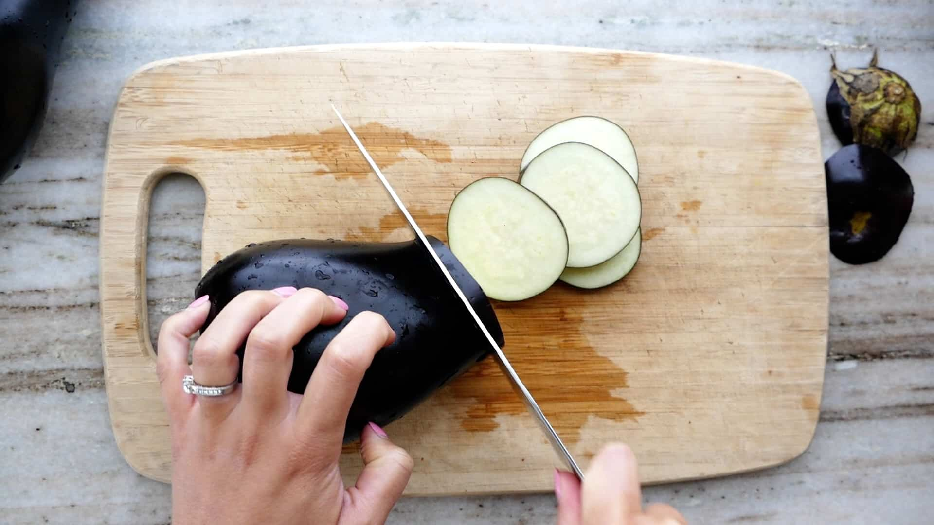 woman slicing an eggplant into rounds over a bamboo cutting board