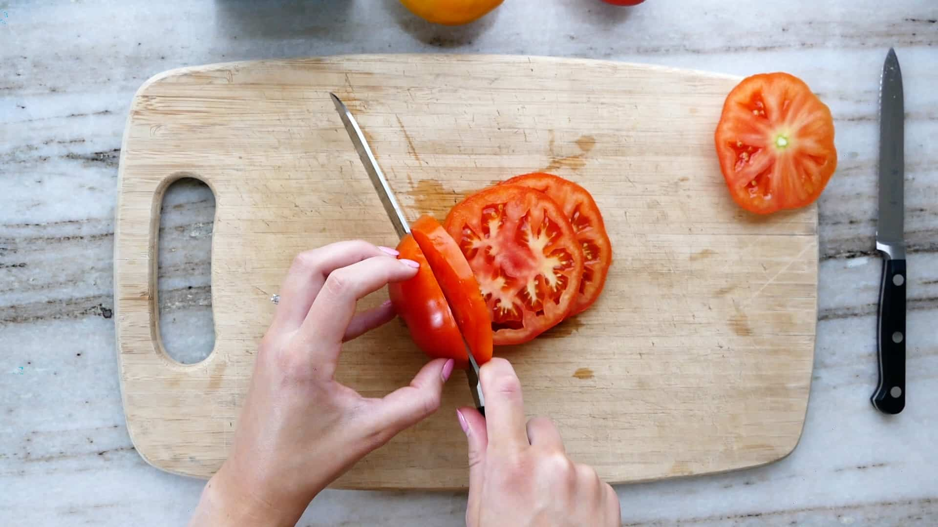 woman slicing a beefsteak tomato with a serrated knife on a cutting board