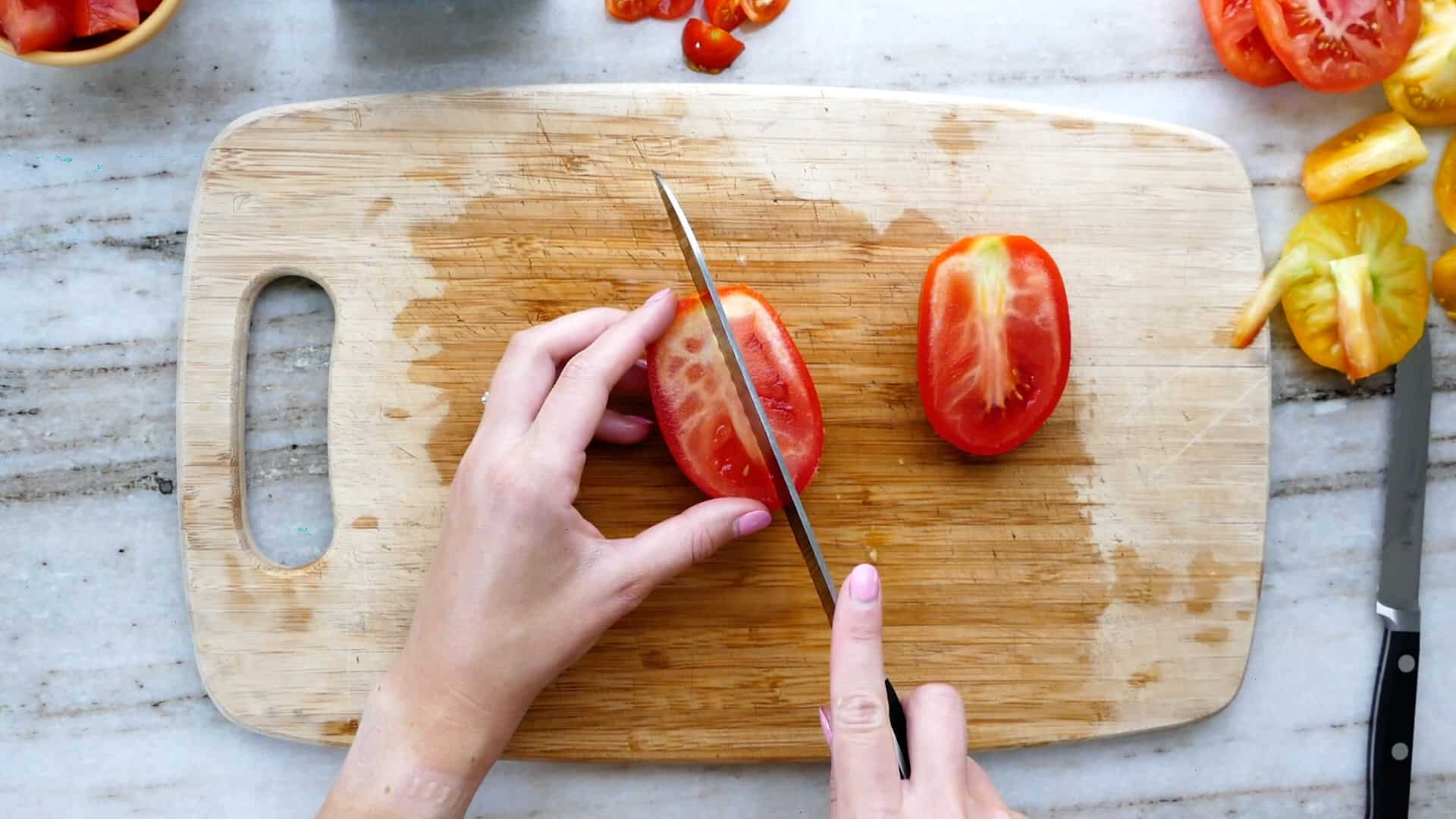 woman slicing a roma tomato into quarters on a cutting board