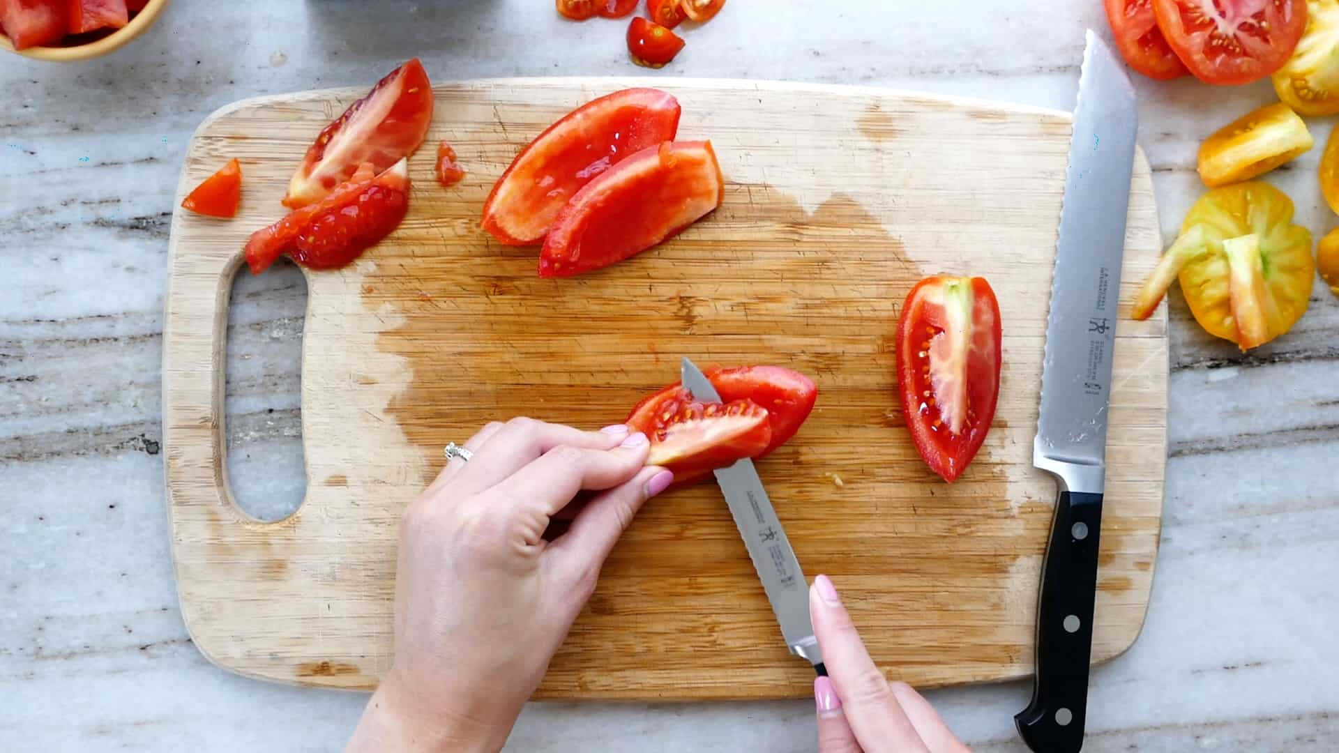 woman removing the seeds from a roma tomato on a cutting board
