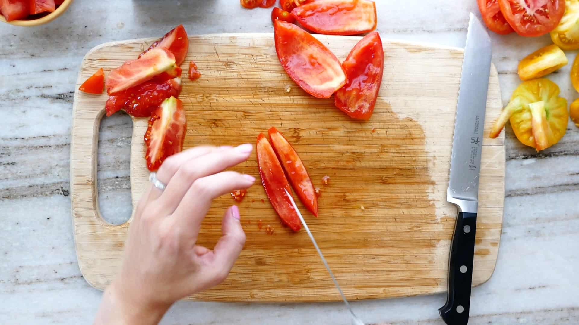 woman slicing a roma tomato into strips on a cutting board