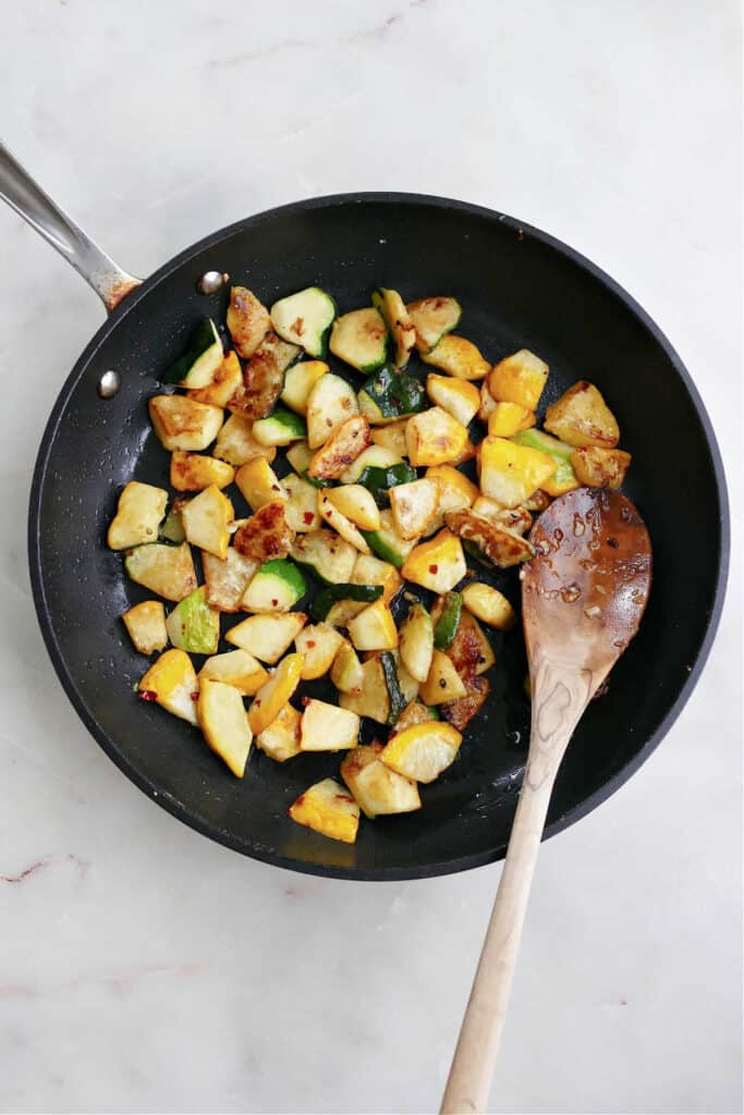 diced patty pan squash cooking in a skillet with a wooden spoon on a counter