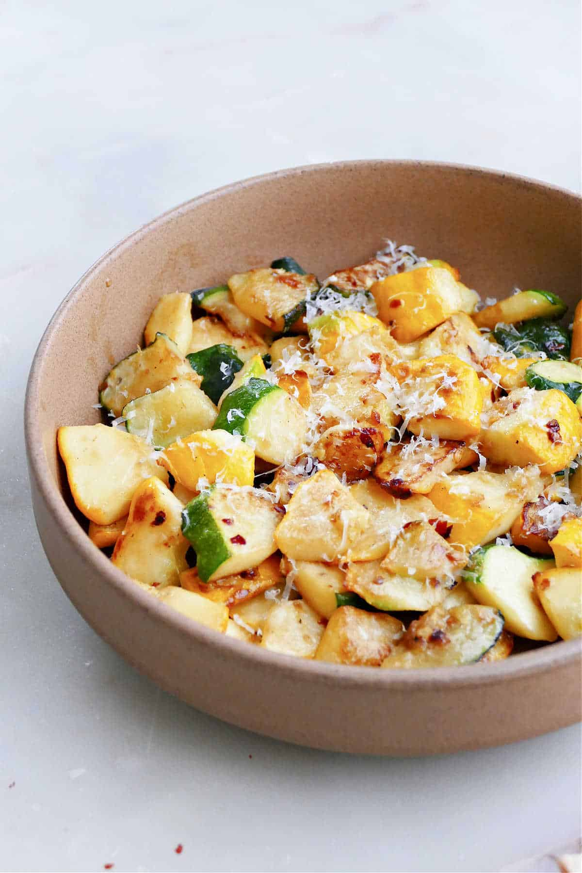 patty pan squash cooked in a skillet and topped with parmesan cheese and red pepper flakes