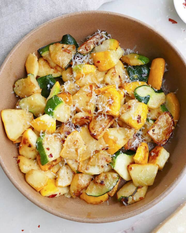 sauteed patty pan squash with parmesan cheese in a serving bowl on a counter