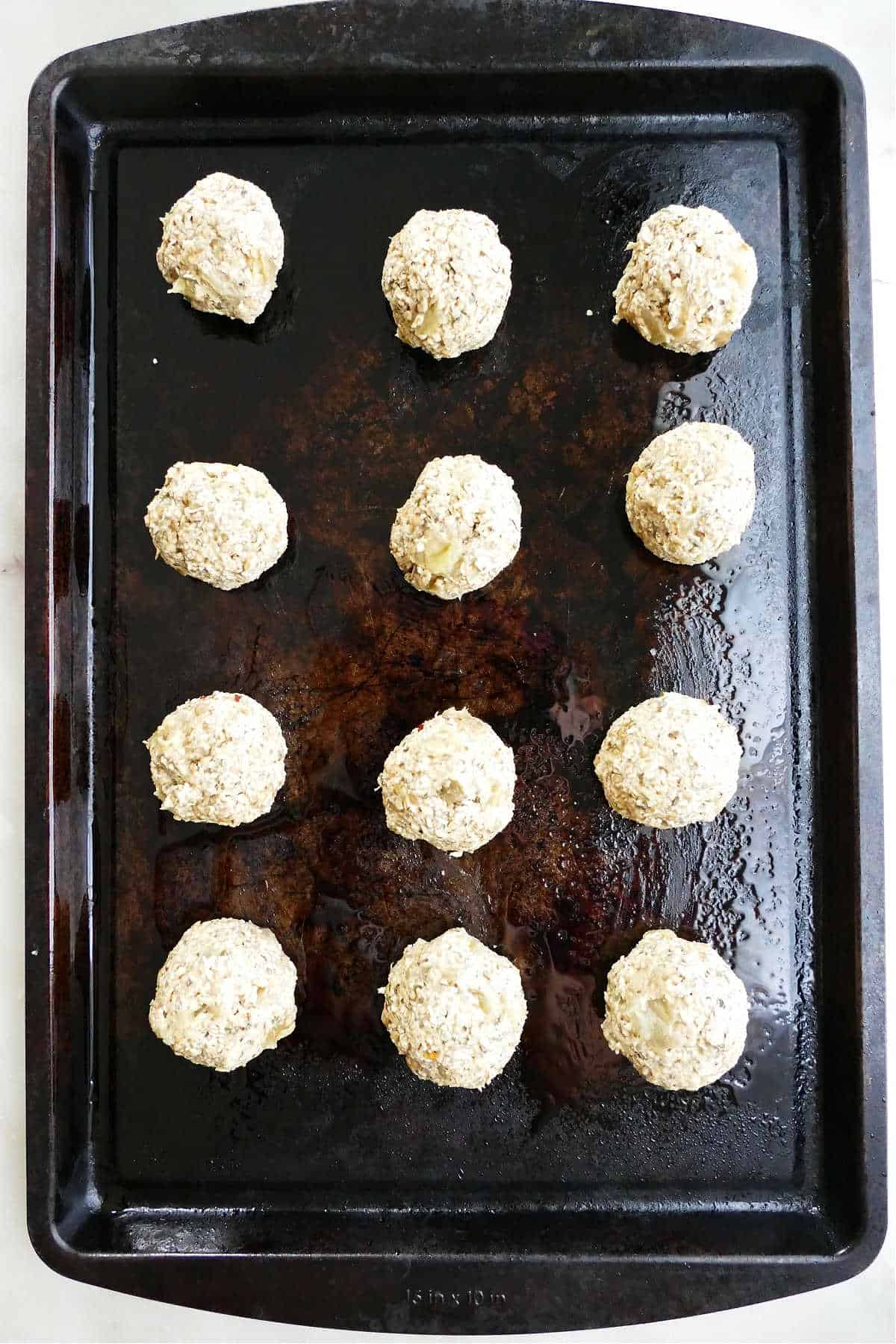 12 eggplant meatballs on a greased baking sheet before going into the oven