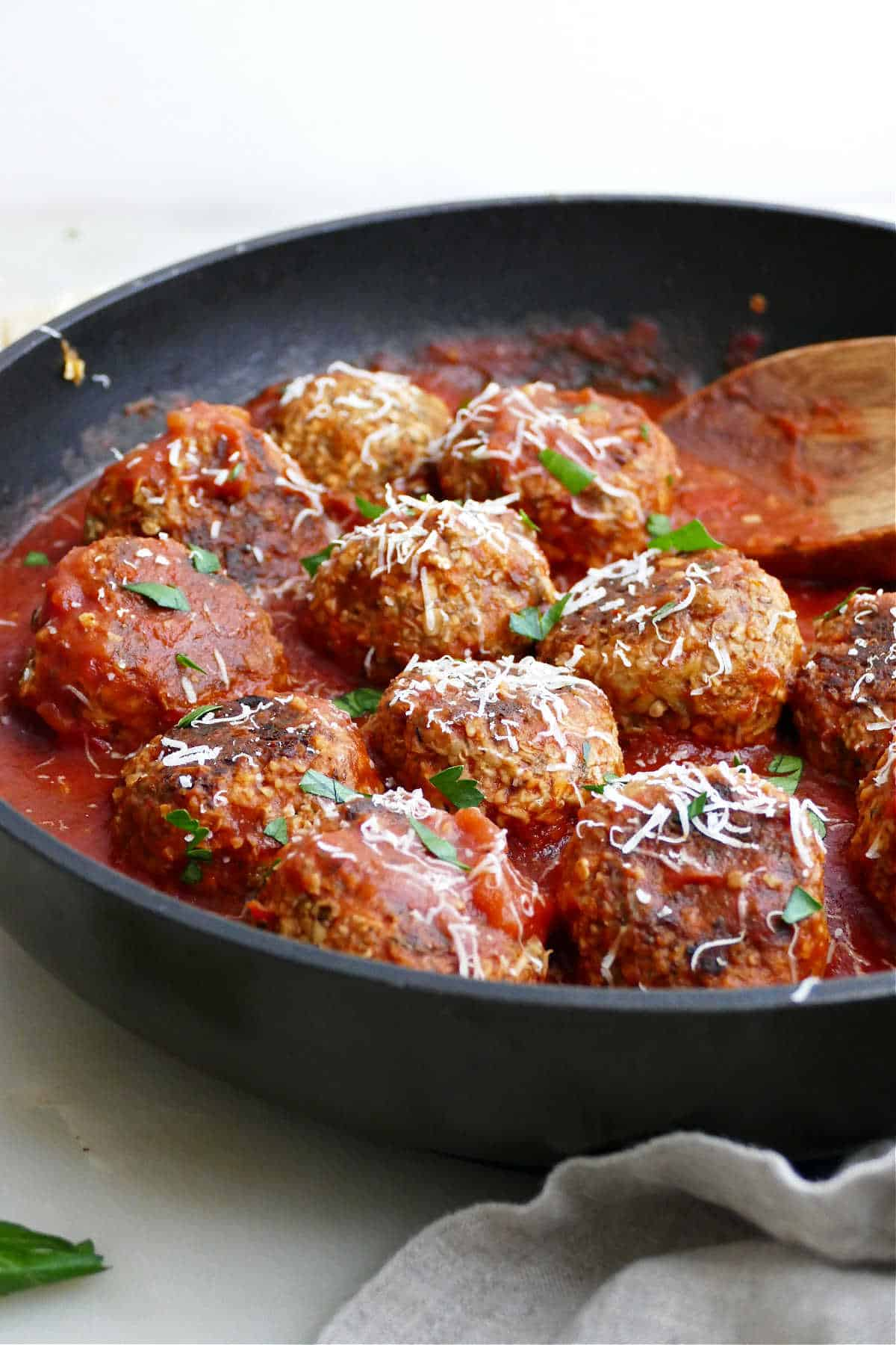 eggplant meatballs in a skillet simmering in tomato sauce and topped with parsley