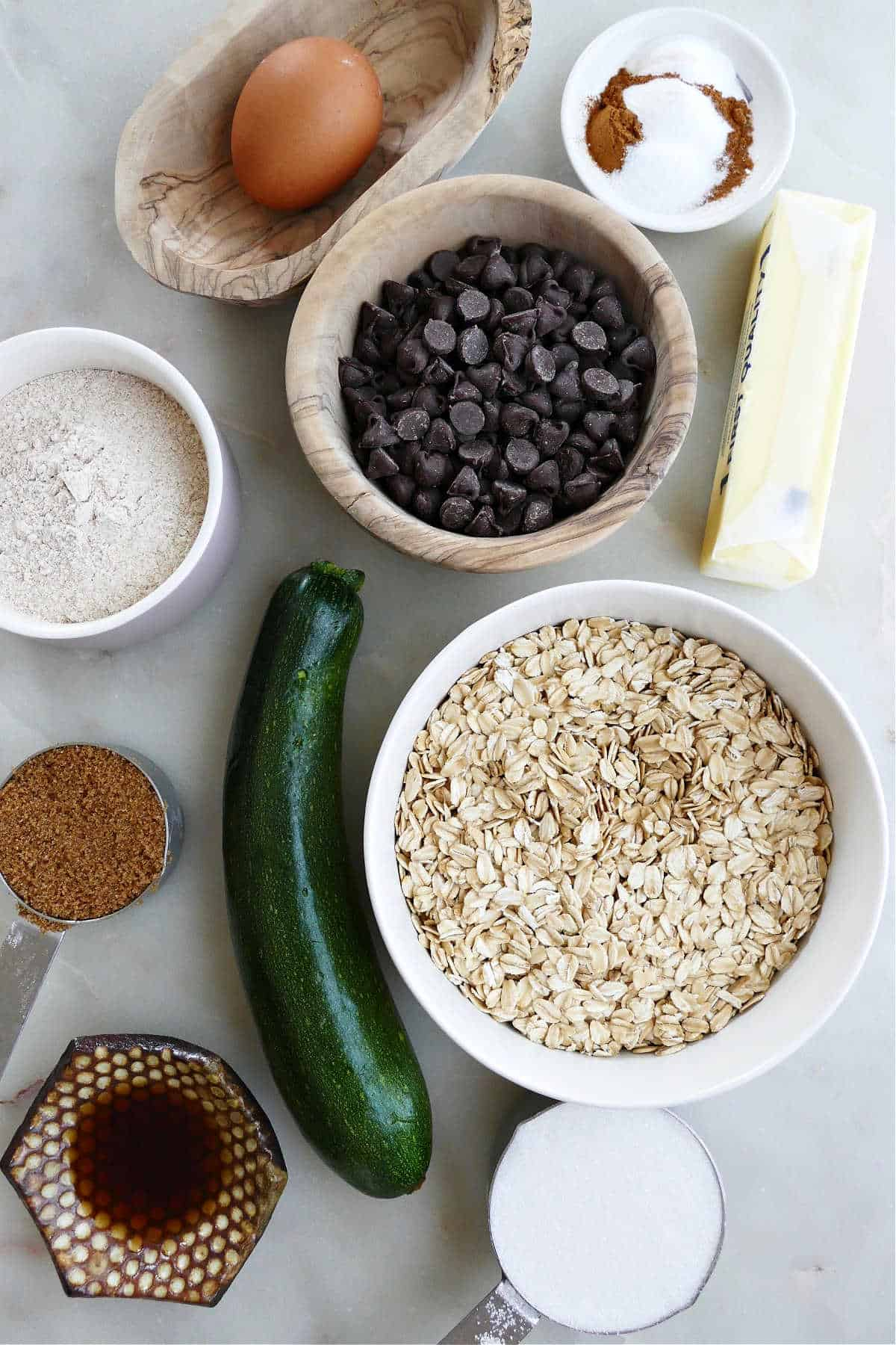 oats, zucchini, chocolate chips, and other ingredients for cookies on a counter