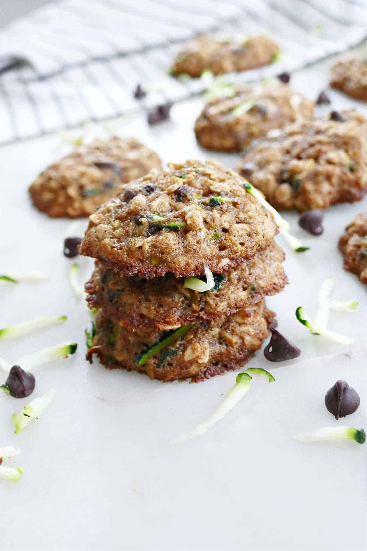 three zucchini chocolate chip cookies stacked on top of each other on a counter