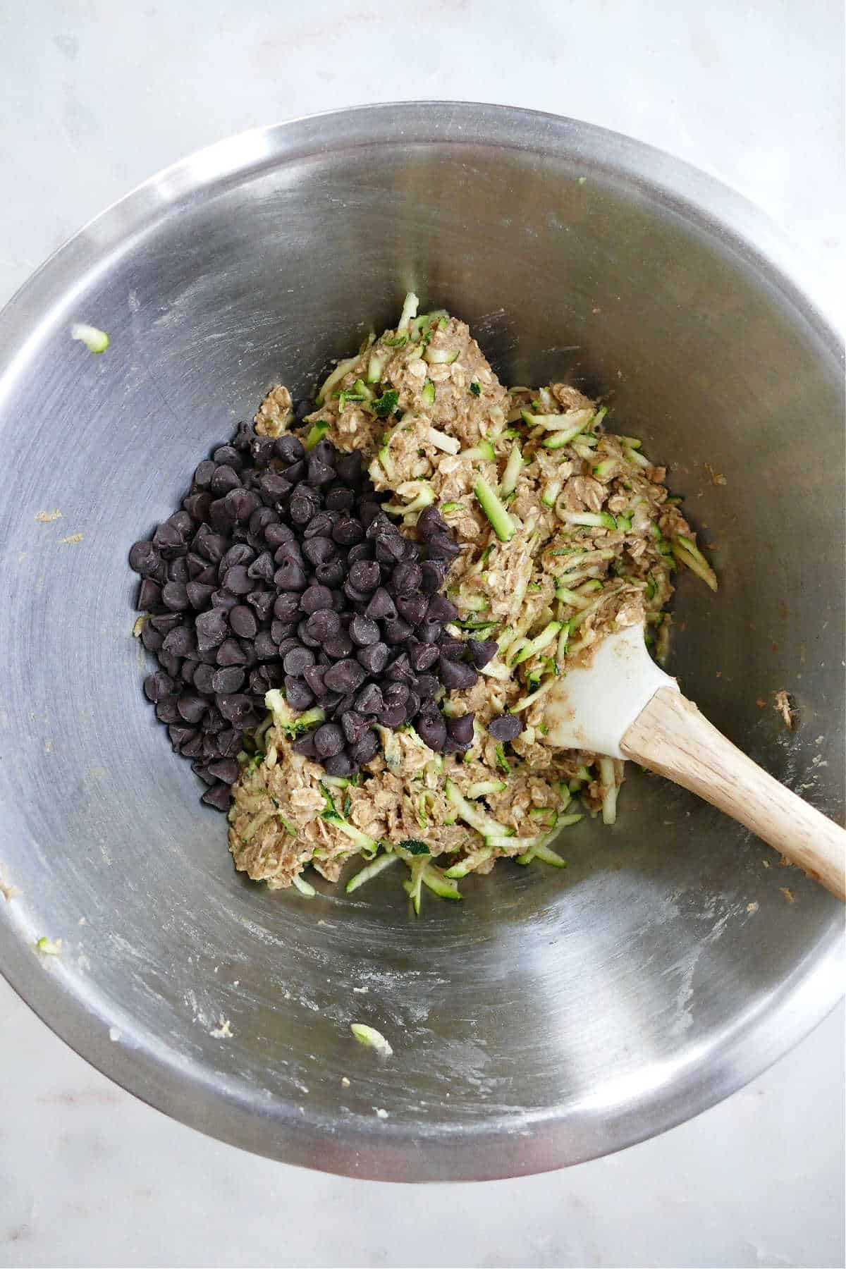 shredded zucchini and chocolate chips being mixed into cookie batter with a spatula
