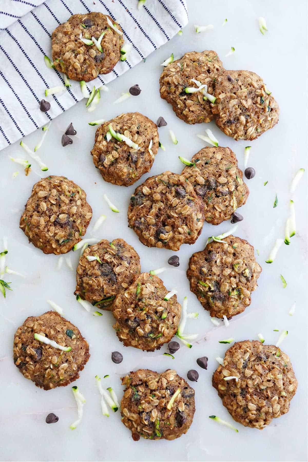 zucchini chocolate chip cookies spread out on a counter next to a napkin and shredded zucchini