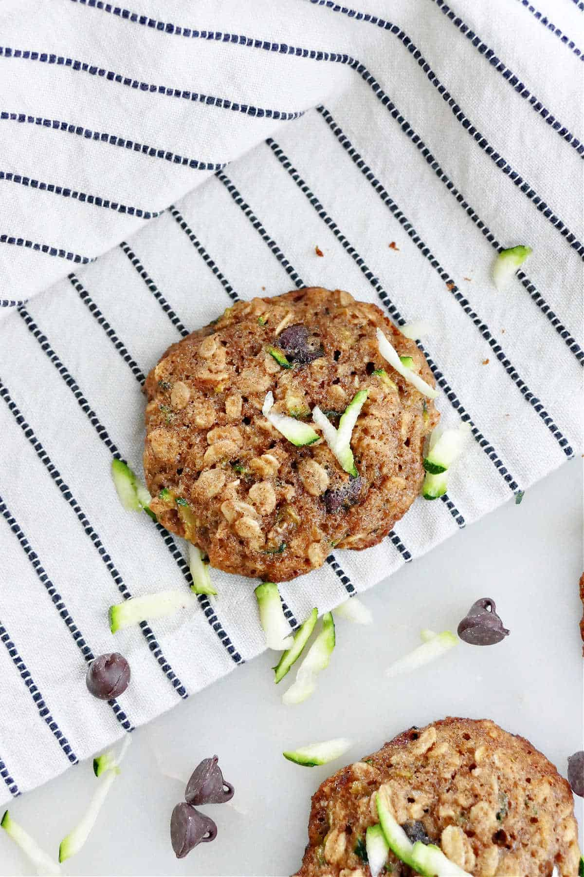 zucchini chocolate chip cookie on a striped dish towel on a counter