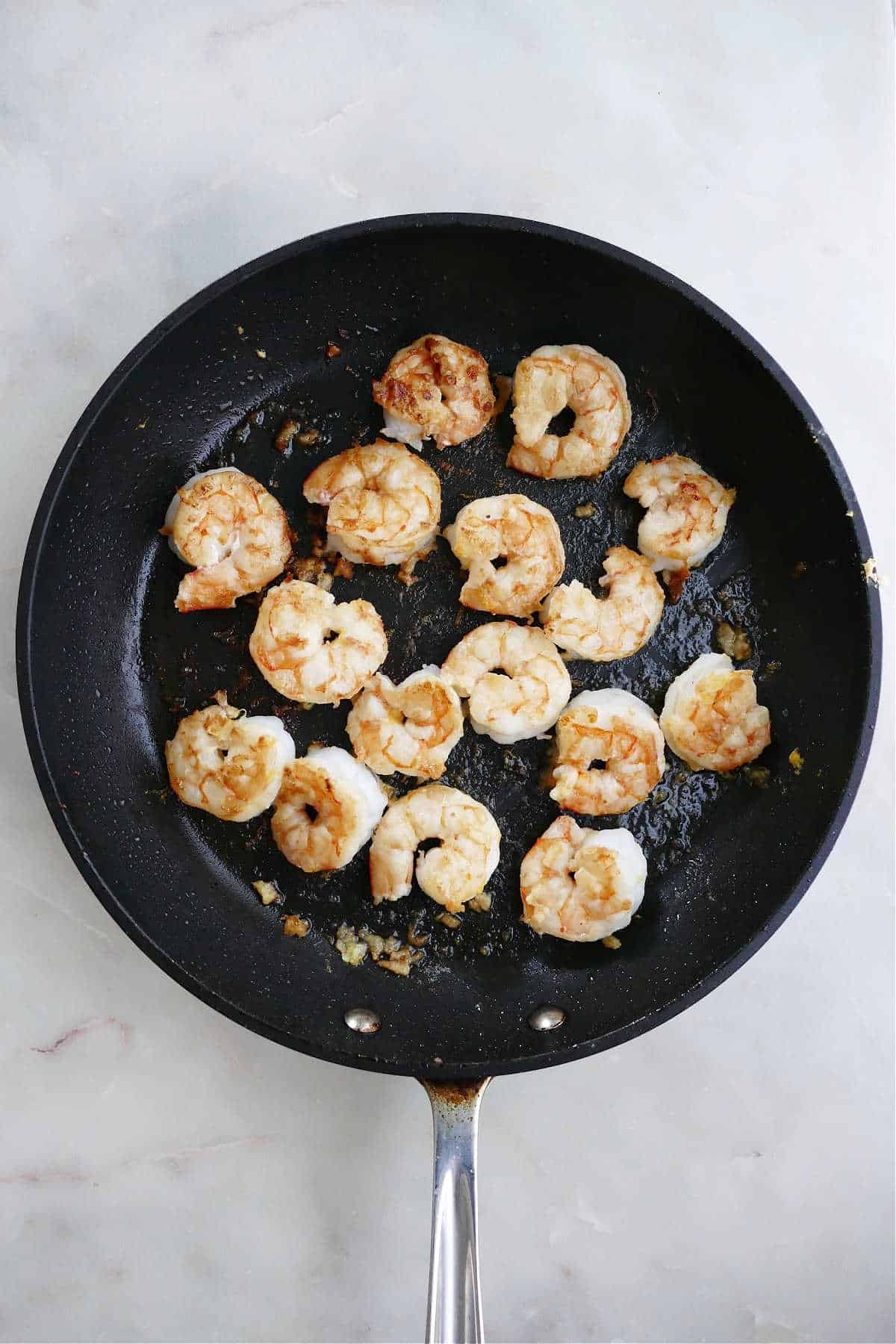 shrimp cooking in lemon garlic butter in a skillet on a counter