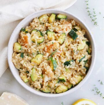 zucchini risotto with shrimp in a serving dish on a counter next to ingredients