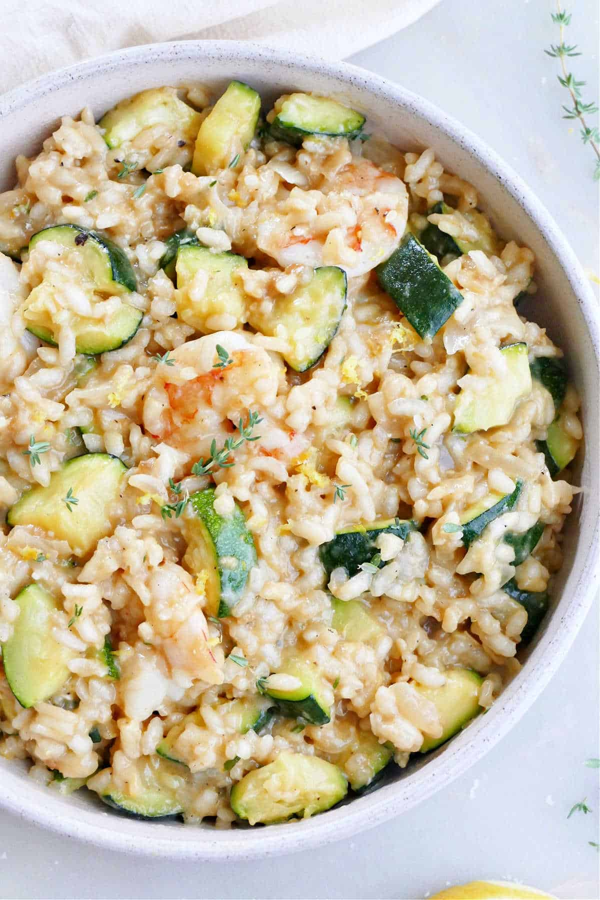 zucchini and shrimp risotto in a serving bowl on a counter