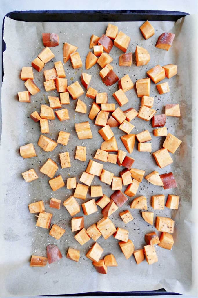 cubed sweet potato tossed in oil and salt on a lined baking sheet