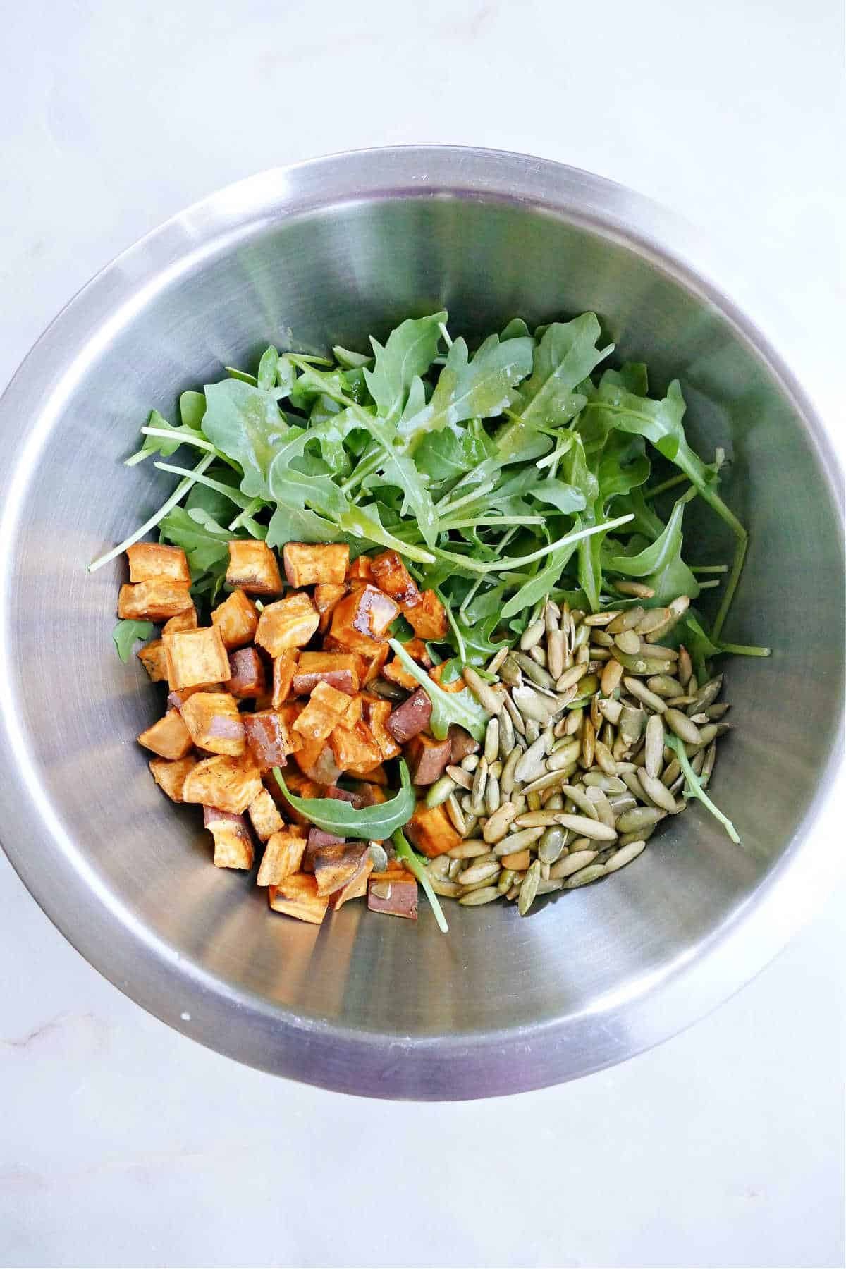 roasted sweet potato, arugula, and pumpkin seeds in a mixing bowl on a counter