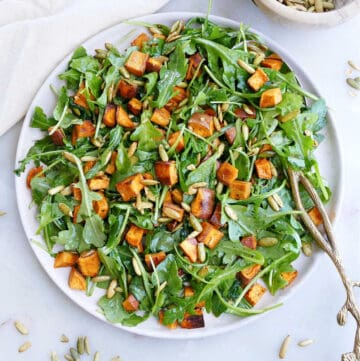 arugula sweet potato salad on a large serving dish with a spoon on a counter