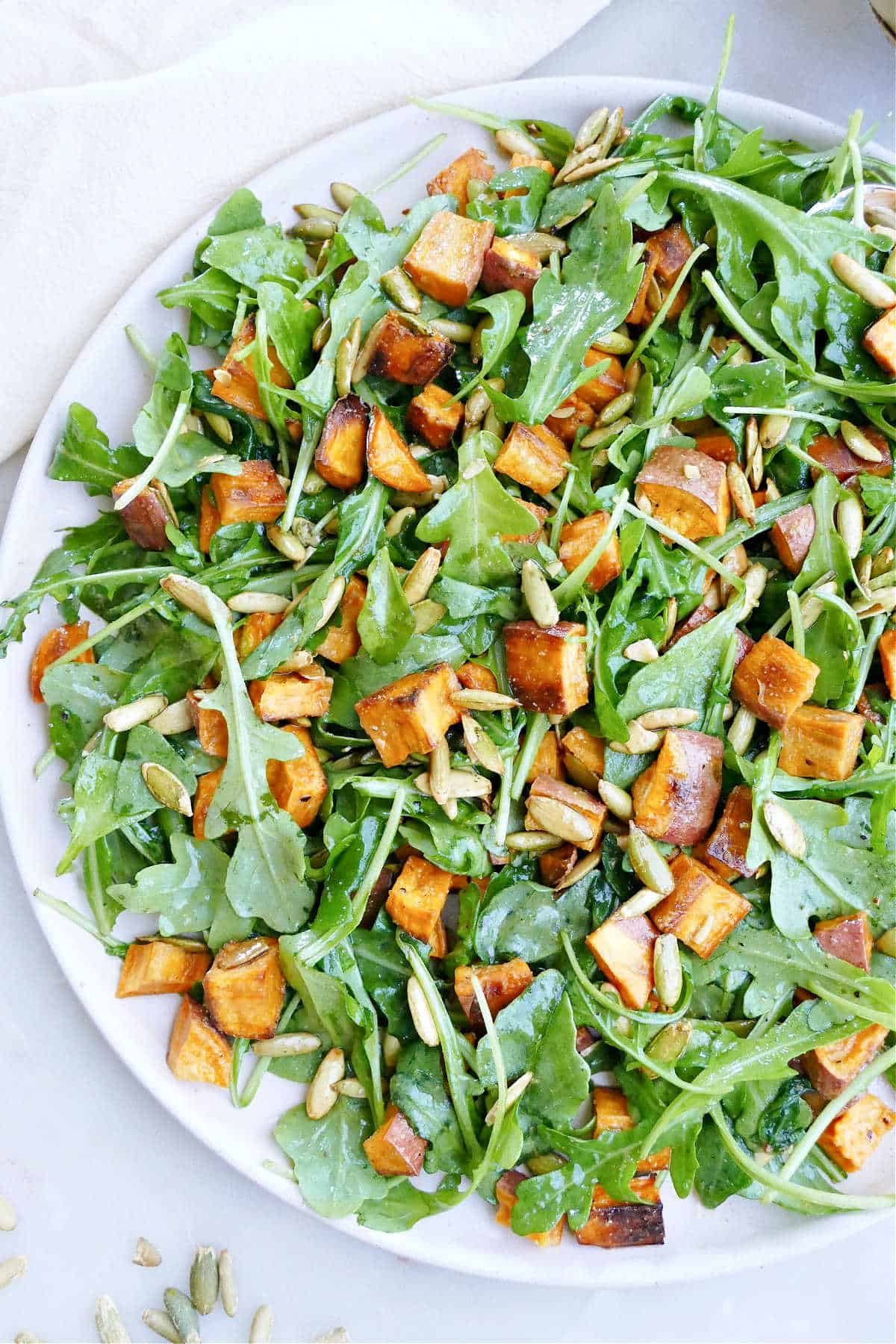 arugula sweet potato salad topped with pumpkin seeds on a large serving dish
