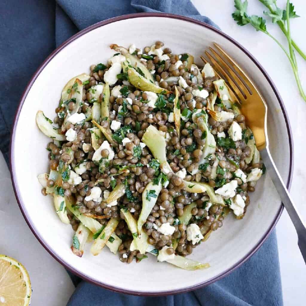 fennel lentil salad in a serving bowl with a fork on top of a napkin