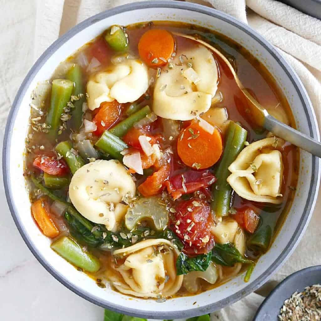 vegetable tortellini soup in a serving bowl with herbs and a spoon
