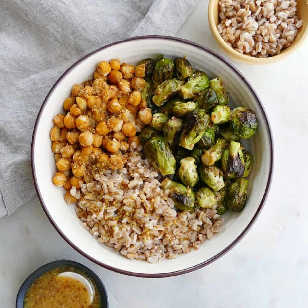 brussels sprouts, chickpeas, and farro in a serving bowl on a counter