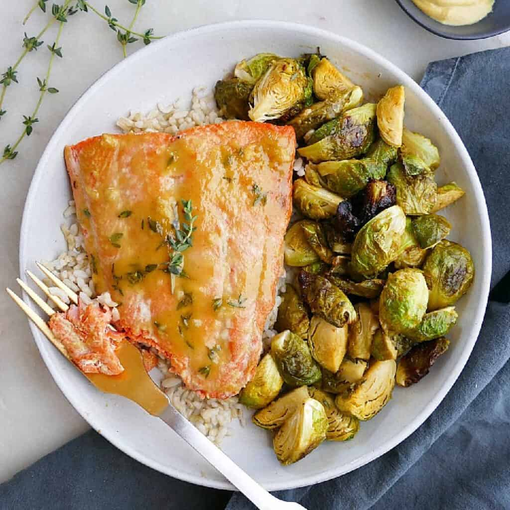 maple mustard salmon and Brussels sprouts on a plate with a fork