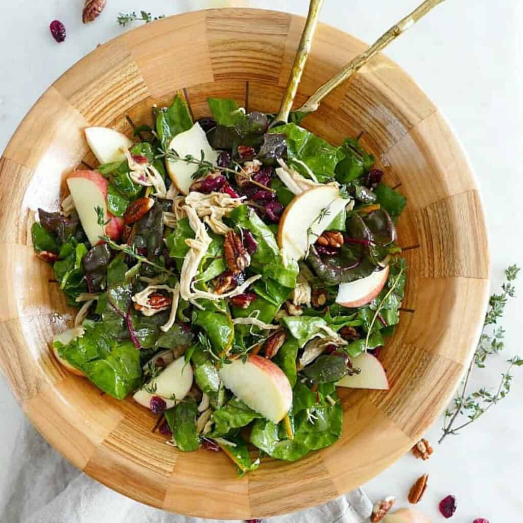 maple swiss chard salad with turkey in a bowl with salad utensils