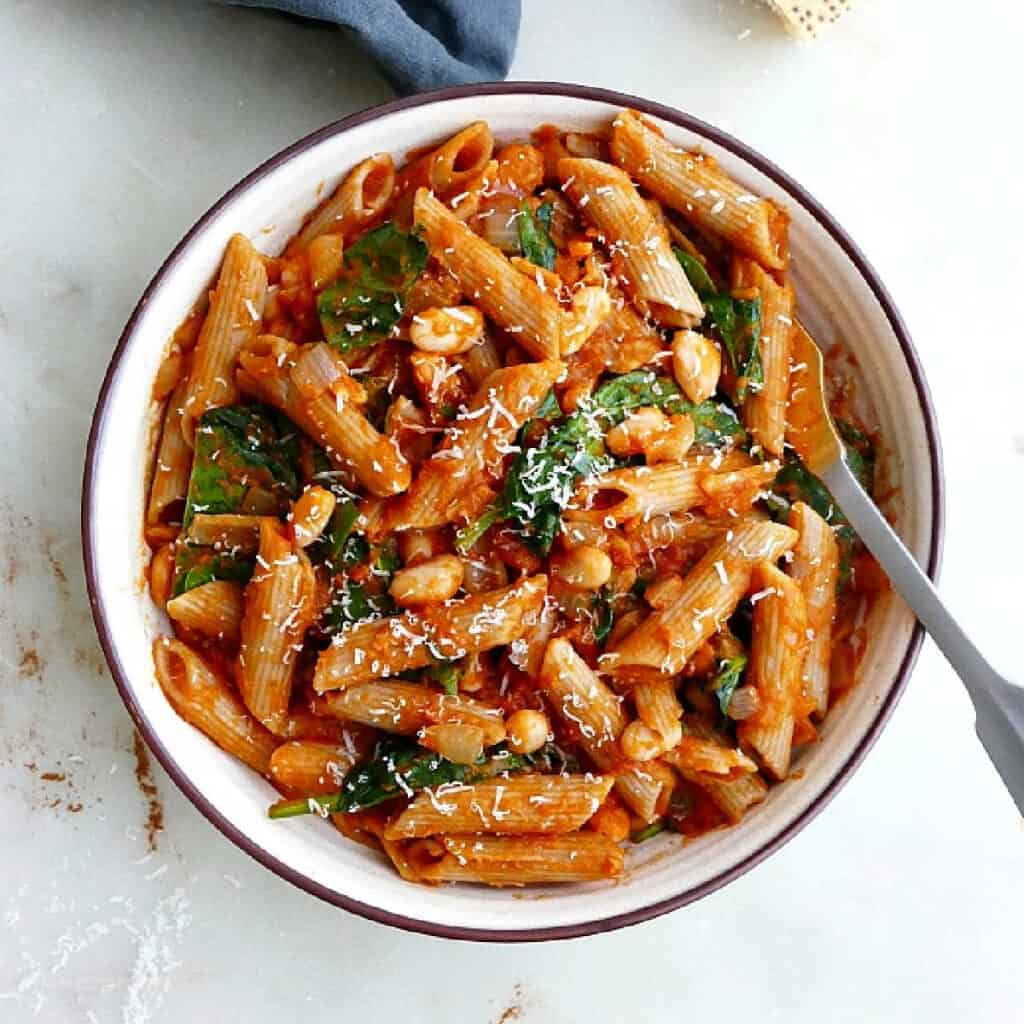 pumpkin tomato pasta with spinach and white beans in a serving bowl with a spoon