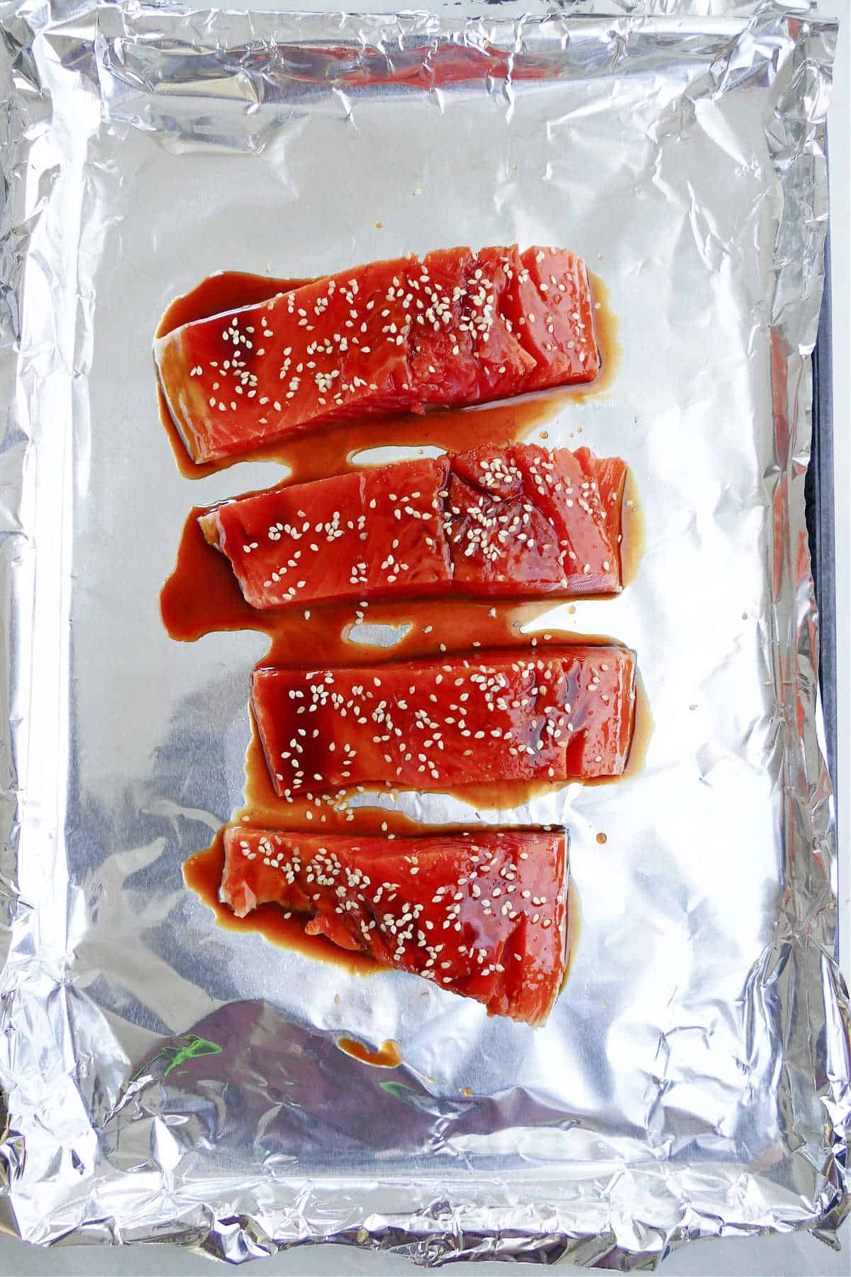 four salmon fillets spread with teriyaki sauce and topped with sesame seeds on a foil lined baking sheet
