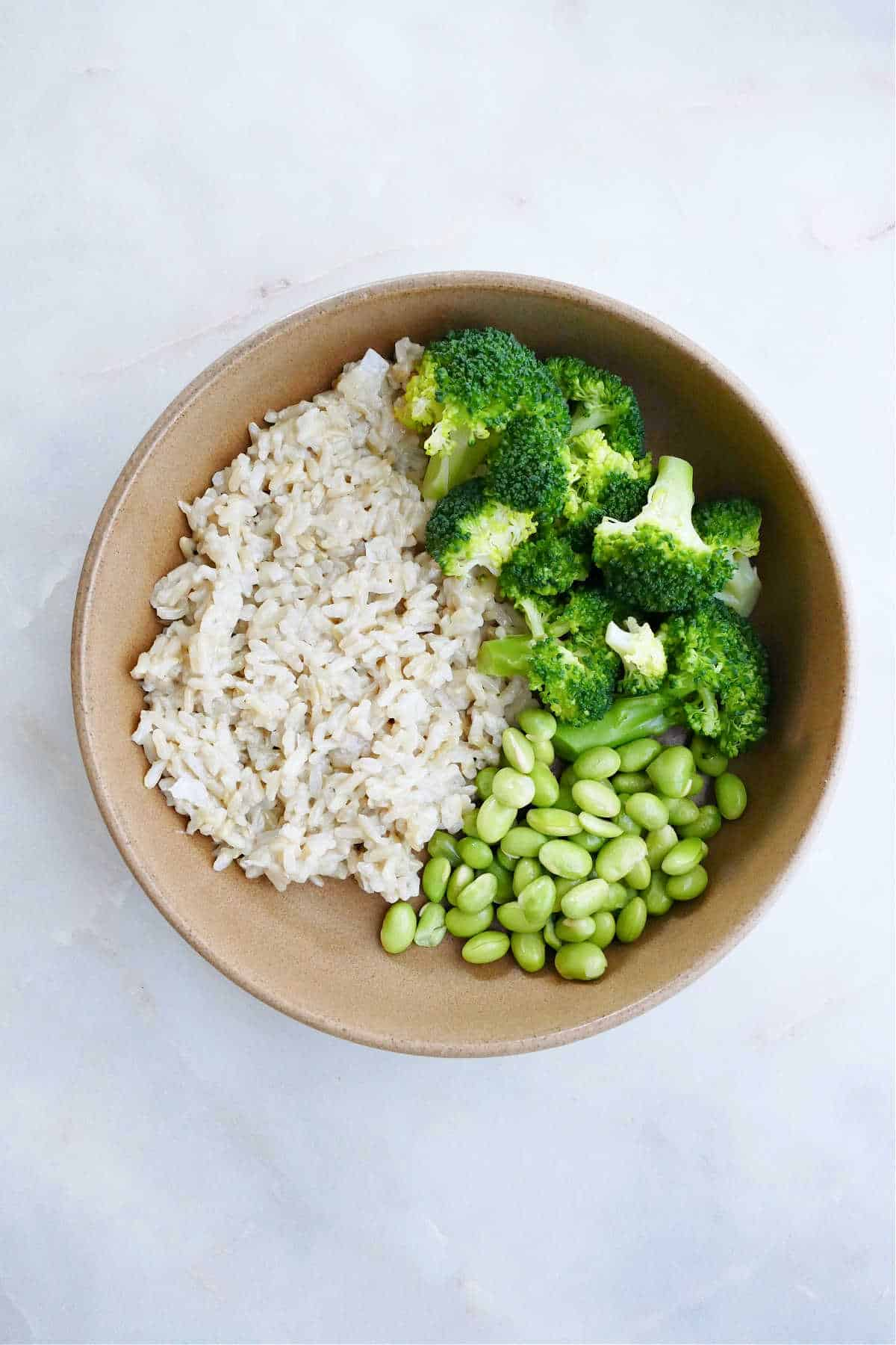 serving bowl with coconut rice, steamed broccoli, and edamame on a counter