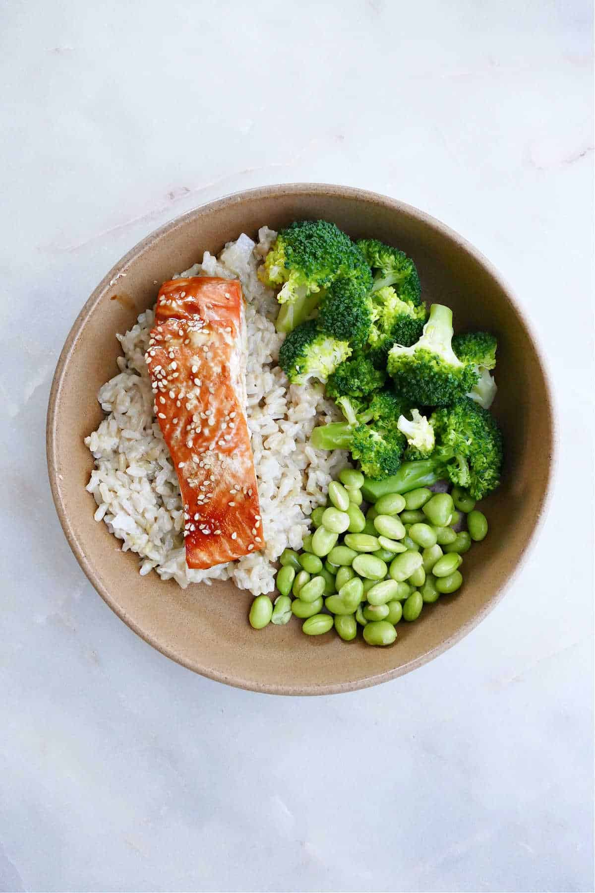 serving bowl with coconut rice, broccoli, edamame, and teriyaki salmon on a counter