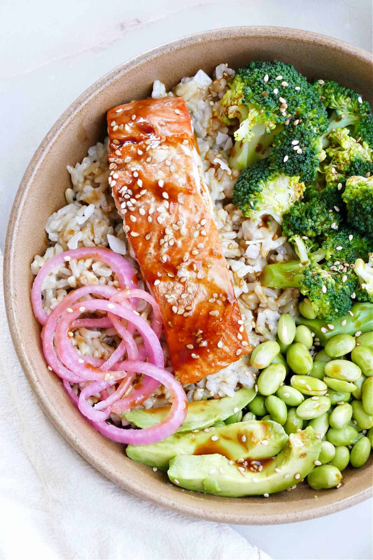 teriyaki salmon, pickled onions, broccoli, edamame, and avocado over rice in a serving bowl