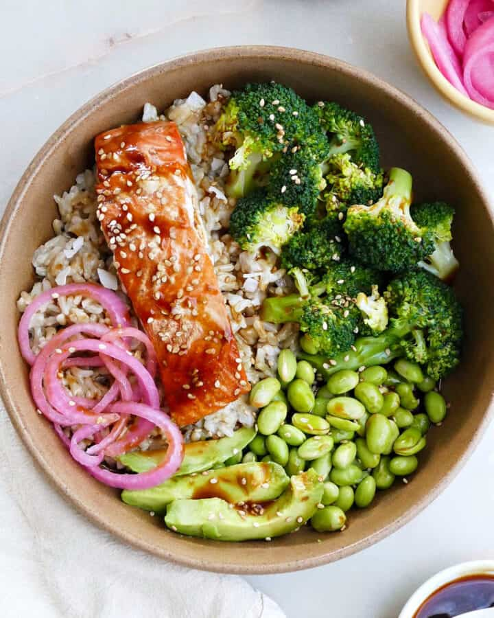 salmon teriyaki bowl topped with avocado and pickled red onions on a counter