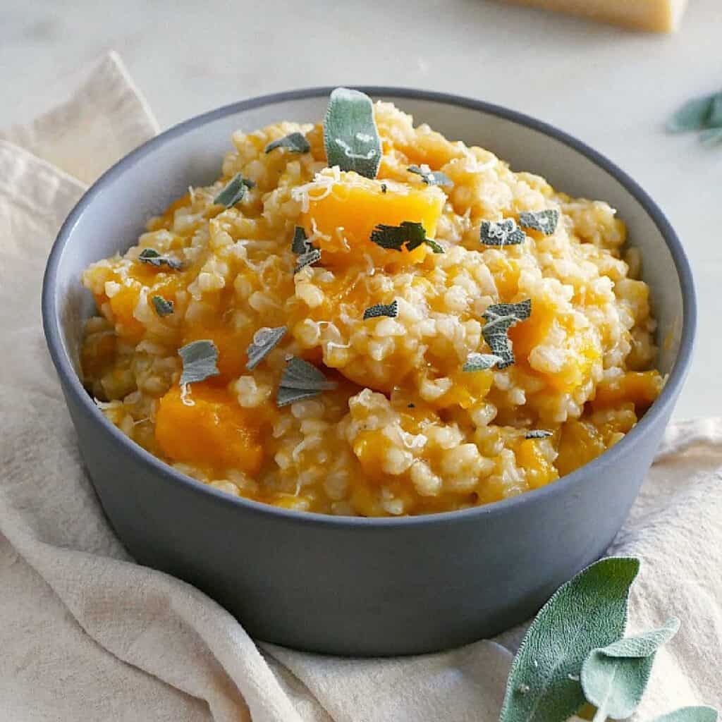 slow cooker butternut squash risotto in a serving dish topped with sage