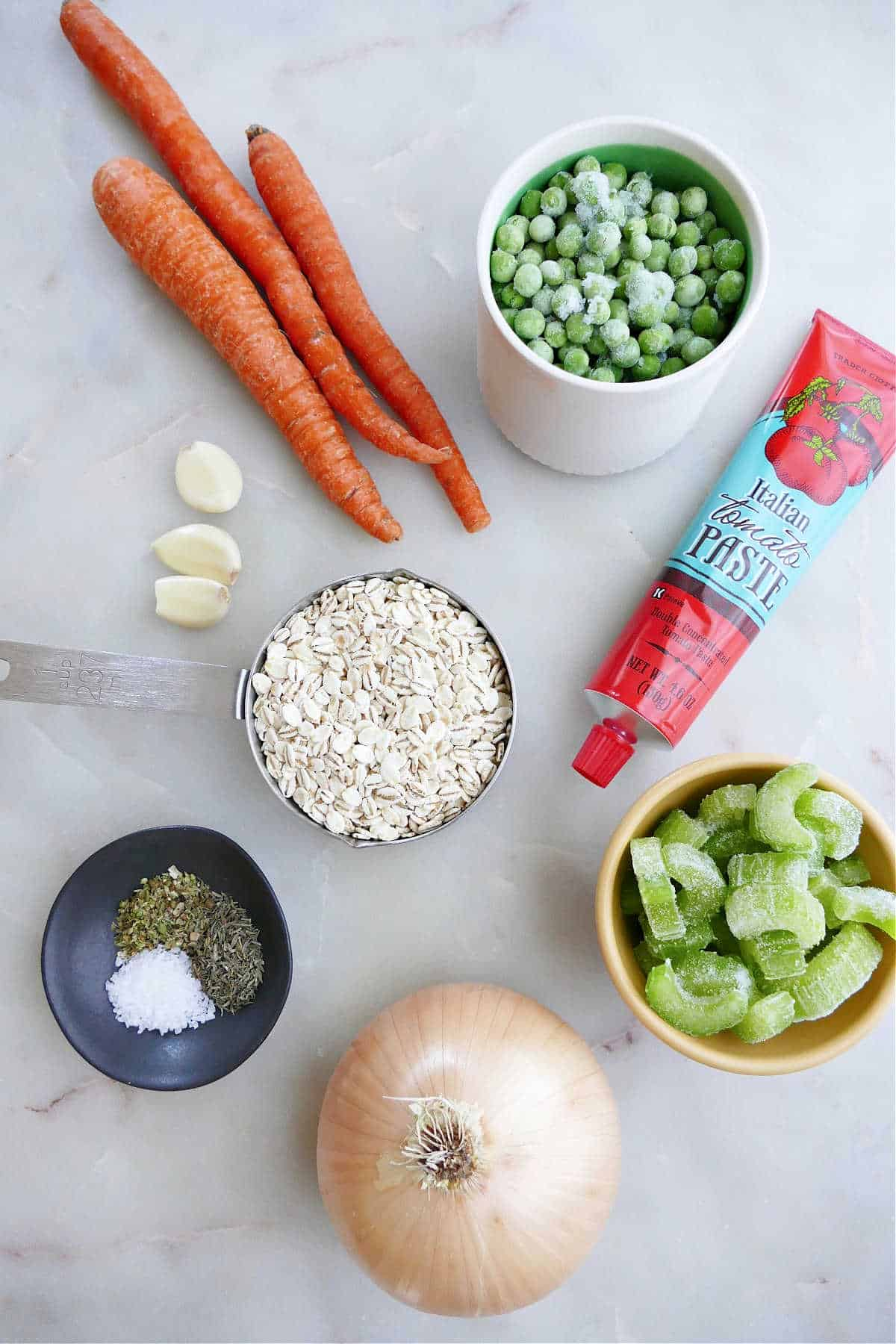 carrots, celery, tomato paste, barley, garlic, celery, onion, and seasonings on a counter
