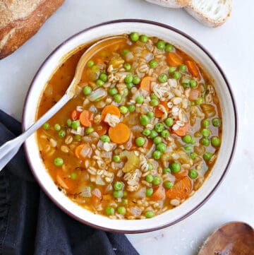 barley soup with vegetables in a serving bowl with a spoon next to bread