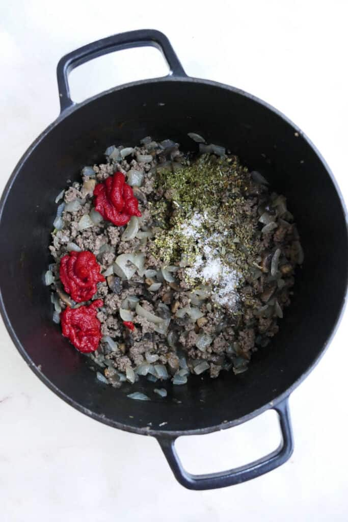 ground beef and veggies cooking in a soup pot with seasonings and tomato paste