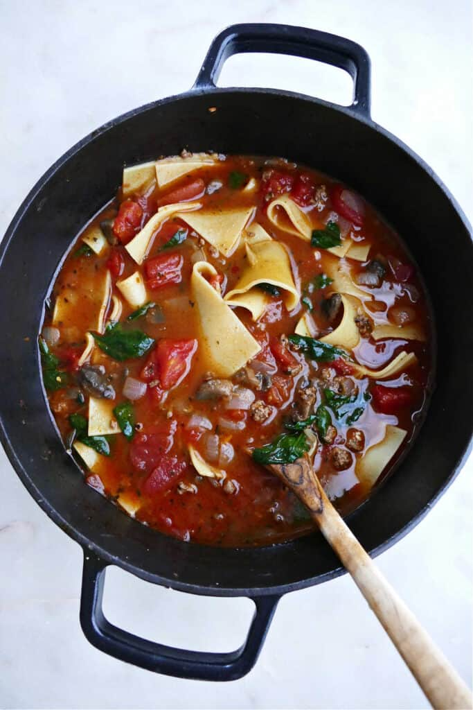 lasagna soup cooking in a soup pot and being stirred with a wooden spoon