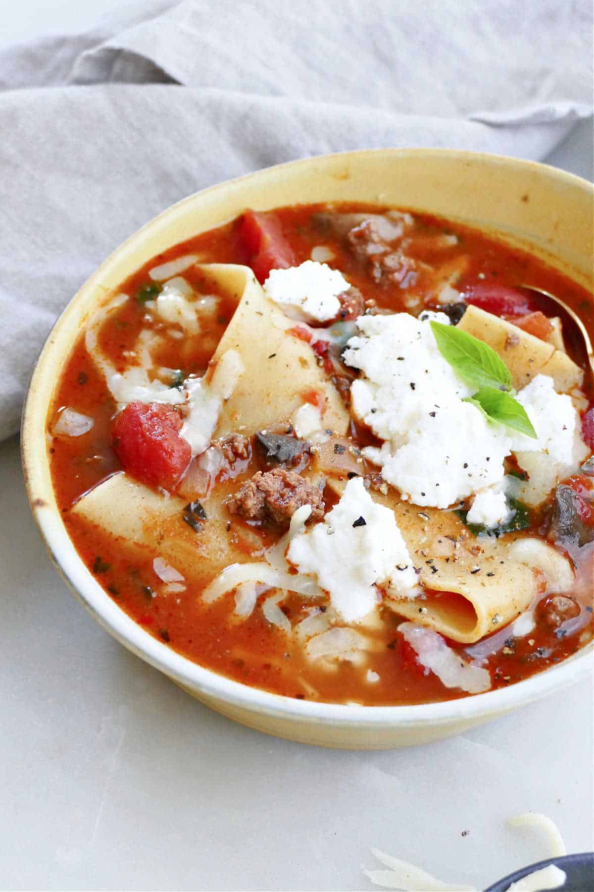 veggie and beef lasagna soup in a serving bowl on a counter next to a napkin