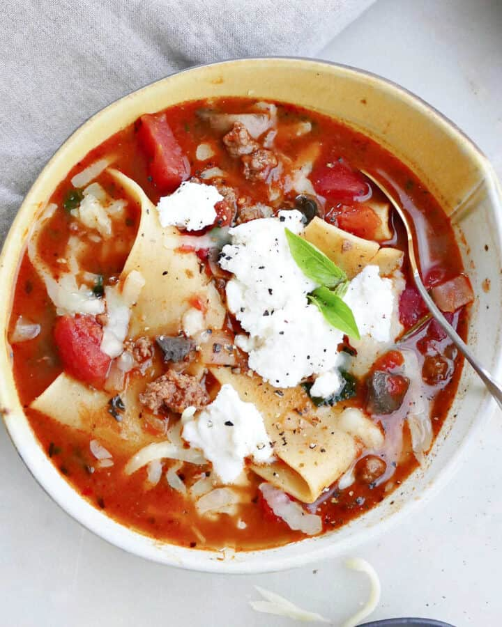 one pot lasagna soup in a serving bowl topped with ricotta cheese and basil