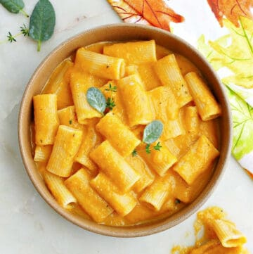 slow cooker butternut squash mac and cheese in a serving bowl topped with sage and thyme